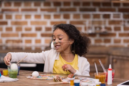african american kid painting easter egg in glass with paint