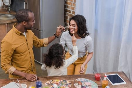 african american daughter and father painting mother face with paints