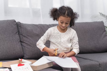 african american kid cutting paper for greeting card on mothers day