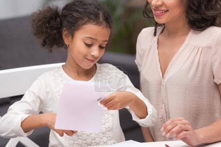 cropped image of african american daughter cutting paper for greeting card