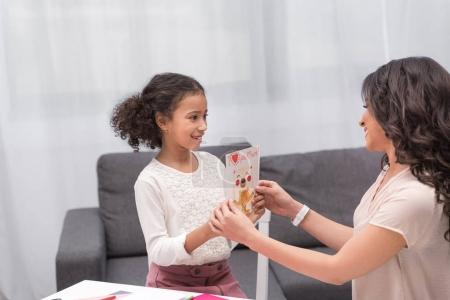 african american daughter presenting greeting card to mother on mothers day