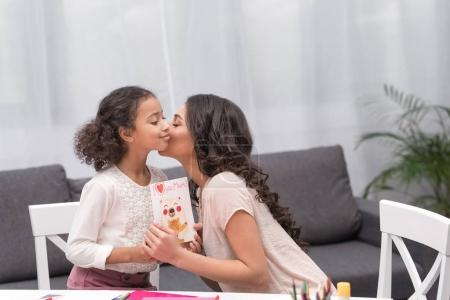 Photo for African american mother kissing daughter for greeting card on mothers day - Royalty Free Image