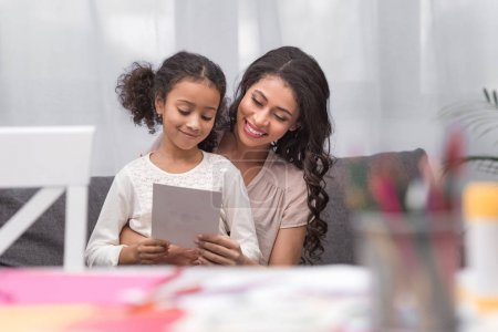 african american mother and daughter looking at greeting card on mothers day