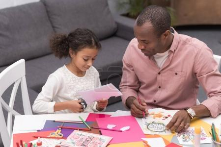 african american daughter cutting paper for greeting card on mothers day