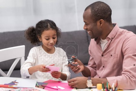 smiling african american father and daughter cutting paper for greeting card on mothers day