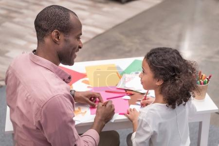 african american father and daughter making greeting card on mothers day and looking at each other