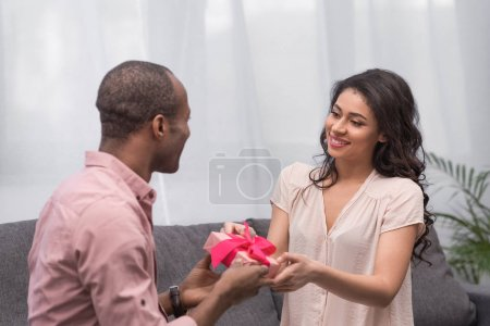 african american boyfriend presenting gift to girlfriend on international womens day