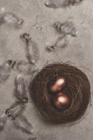 Top view of golden easter eggs in nest with feathers on concrete surface