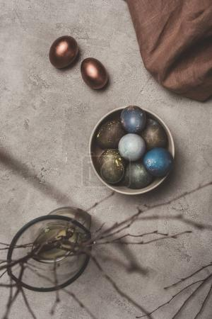 top view of easter eggs and willow branches in vase on concrete surface