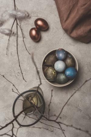 top view of painted easter eggs in bowl and willow branches in vase on concrete surface