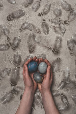 cropped view of man holding easter eggs on concrete surface with feathers