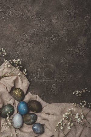top view of easter eggs and flowers on tablecloth on concrete surface