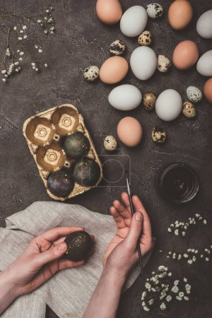 cropped view of man painting easter eggs and putting them into tray, flowers, quail and chicken eggs near