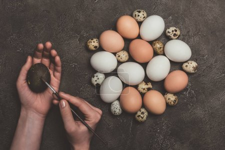 Photo for Cropped view of man painting easter egg, raw quail and chicken eggs near - Royalty Free Image