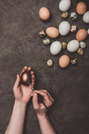 cropped view of man painting golden easter egg, quail and chicken eggs near