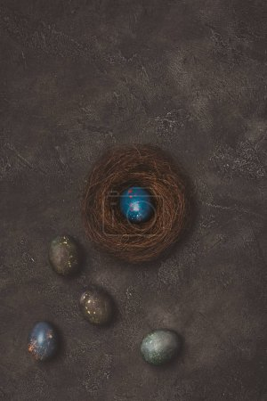 top view of blue easter egg in nest with painted eggs near on concrete table