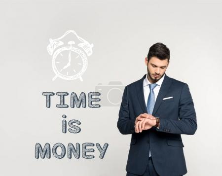 fashionable young businessman checking wristwatch and inscription time is money isolated on grey