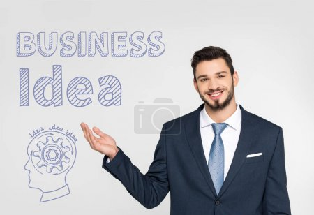 handsome young businessman showing business idea inscription  and smiling at camera isolated on grey