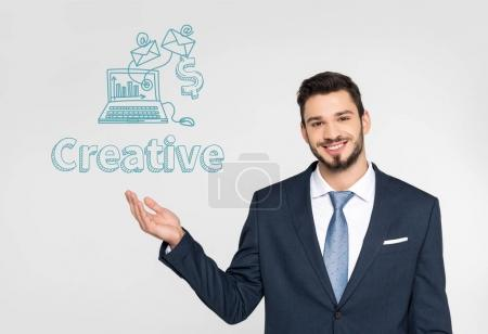 handsome young businessman showing creative icons and smiling at camera isolated on grey