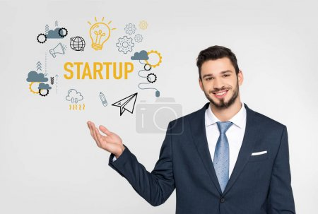 handsome young businessman showing startup icons and smiling at camera isolated on grey