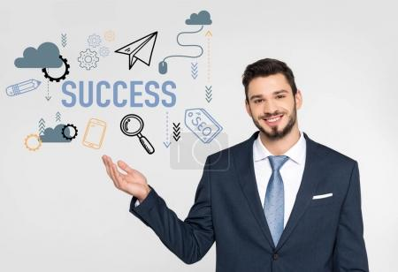 handsome young businessman showing success icons and smiling at camera isolated on grey