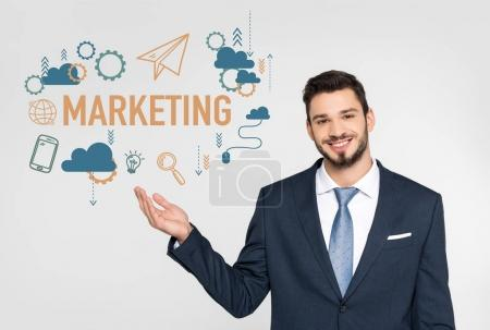 handsome young businessman showing marketing icons and smiling at camera isolated on grey