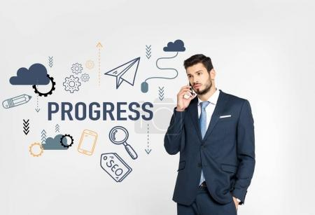 stylish young businessman standing with hand in pocket and talking on smartphone while looking away isolated on grey, progress icons