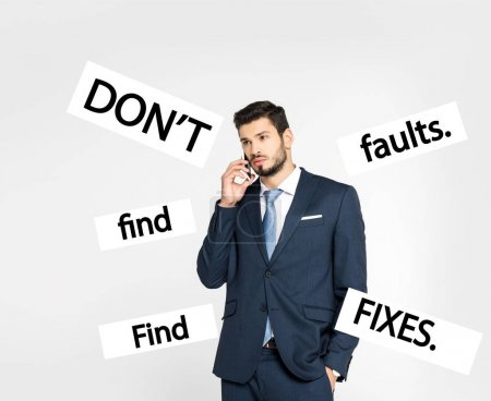 stylish young businessman standing with hand in pocket and talking on smartphone while looking away isolated on grey, dont find faults. find fixes inscription