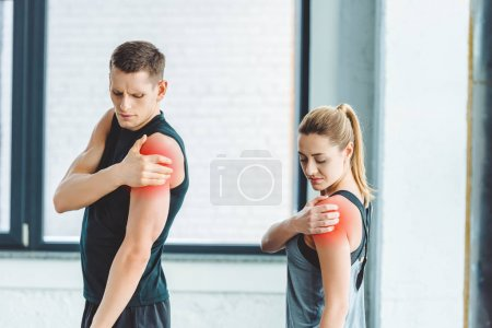 young couple having pain in arms after workout in gym