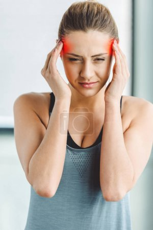 portrait of young woman in sportswear having headache