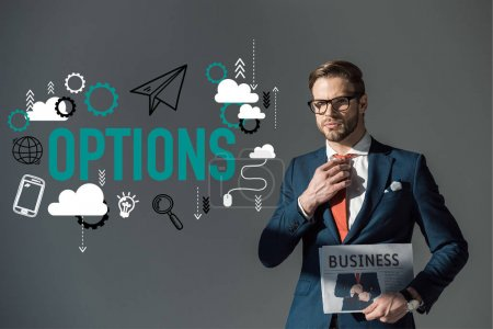 handsome young man in eyeglasses holding newspaper and adjusting necktie, options icons isolated on grey