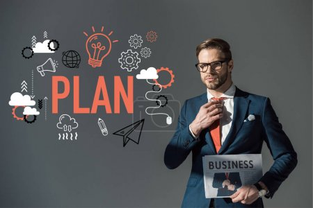 handsome young man in eyeglasses holding newspaper and adjusting necktie, plan icons isolated on grey