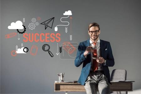 smiling businessman with cup of coffee sitting on table and looking at camera, success icons on grey