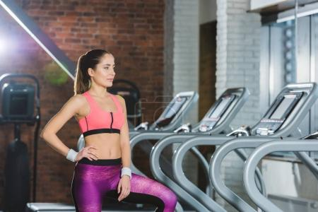 sporty woman standing near treadmill at gym