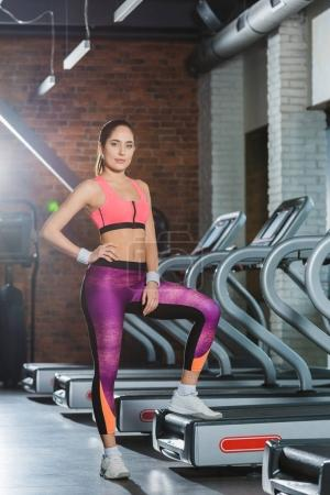 sporty woman standing on treadmill and looking at camera