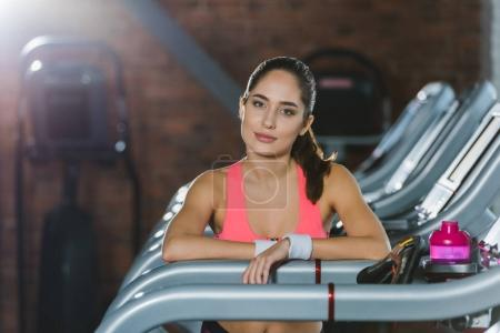 sportswomen lenaing on treadmill railing and looking at camera