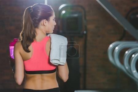 sportswoman standing with towel on shoulder at gym
