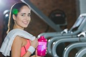 sporty woman standing with shaker and towel in hands against treadmills