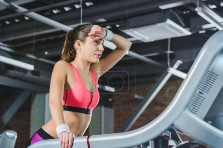 tired sporty woman standing on treadmill at gym
