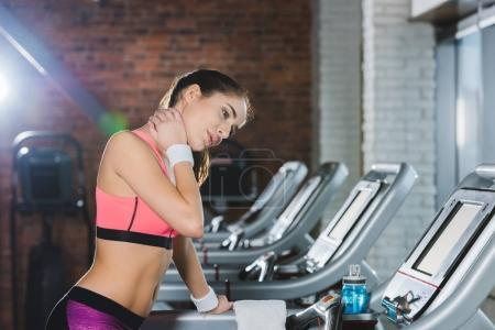 sporty woman touching her neck on treadmill