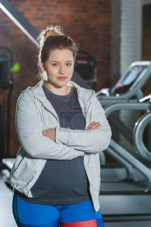 overweight woman standing at gym with arms crossed and looking at camera