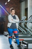 overweight woman standing against treadmills with arms crossed