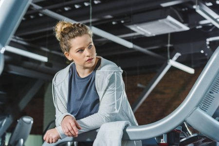 overweight woman leaning on rail of treadmill at gym