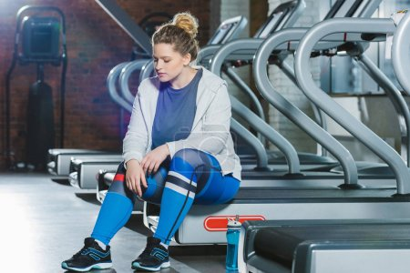 tired overweight woman sitting on treadmill at gym