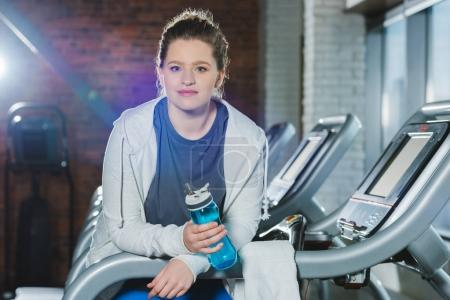 overweight woman holding bottle of water while standing on treadmill and looking at camera
