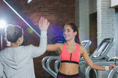 women giving high five against treadmills