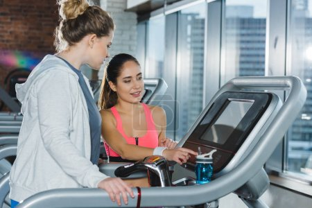 trainer adjusting treadmill before training of overweight woman