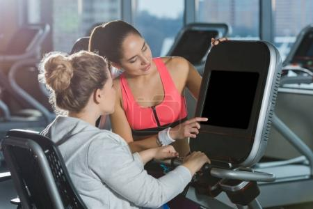 overweight woman starting to doing cardio while trainer helping her