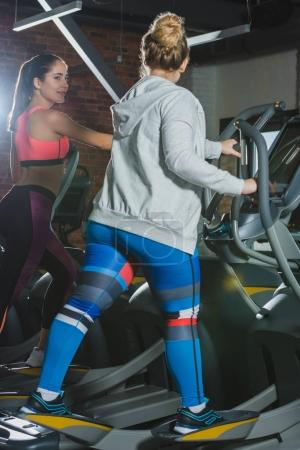 women training on treadmill at gym and looking on each other