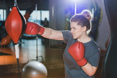 overweight woman having boxing training at gym